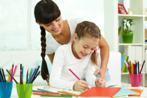 Cette image montre une baby-sitter s'assurant des devoirs de l'enfant qu'elle garde après l'école